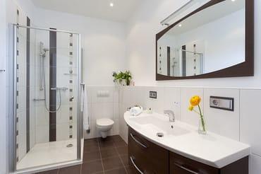 Ein zweites Badezimmer mit hochwertiger Dusche und großzügigem Waschtisch befindet sich ebenfalls in der oberen Etage der Maisonettewohnung.