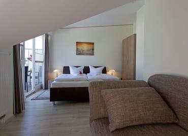 Über eine offene Treppe gelangen Sie vom Wohnbereich in die obere Etage des Appartements zu den beiden Schlafzimmern