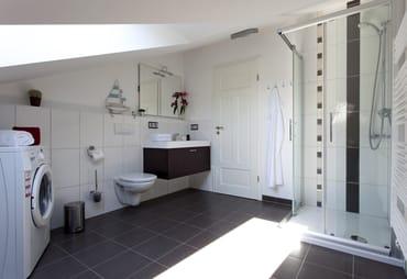 Das moderne Badezimmer ist mit Dusche, WC und einem Haarfön ausgestattet. Zusätzlich verfügt das Appartement über eine eigene Waschmaschine, wodurch der Urlaubskomfort abgerundet wird.