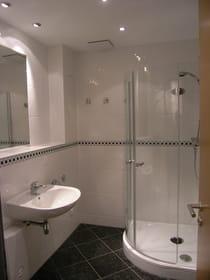 Hochwertig gestaltetes Bad mit Glas-Runddusche, Fußbodentemperierung und Panorama-Spiegel.