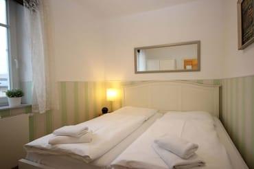Im Schlafraum befinden sich ein schönes Doppelbett, ein Safe und ein Kleiderschrank.
