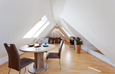 offener Wohn- und Schlafbereich mit gemütlicher Eckcouch und Esstisch für 3 Personen
