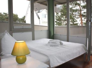 kleines Schlafzimmer mit Zugang zum Balkon
