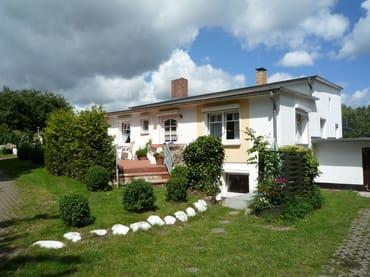 Die weiße Steinreihe läuft auf Ihre möblierte Terrasse rechts unten am Haus zu.