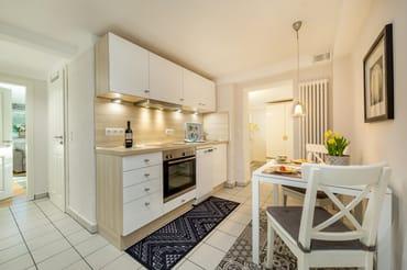 Die schöne Küchenzeile mit weißen Hochglanzfronten bietet Geschirrspüler ...