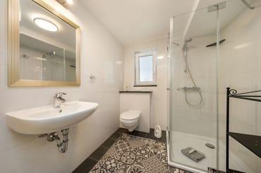 Das schicke Bad mit Echtglasdusche, Handtuchtrockner, Waschbecken, WC und Fenster.