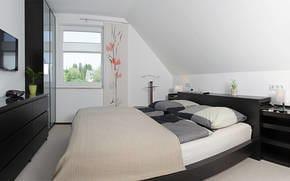 Das Schlafzimmer verfügt über ein komfortables Doppelbett und genügend Stauraum für Ihre Habseligkeiten. Ein Flat-TV rundet die stilvolle Einrichtigung ab.