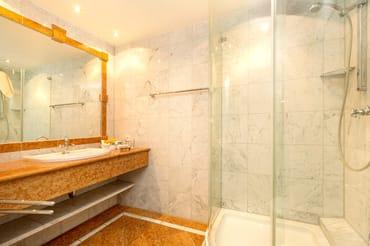 Das schöne marmorgeflieste Bad hat Echtglasdusche, Waschtisch und WC.