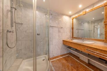 Das marmorgeflieste Bad hat Dusche, WC und einen breiten Waschtisch.