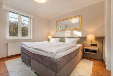 ... Doppelbett und Plissees zum Abdunkeln an den Fenstern.