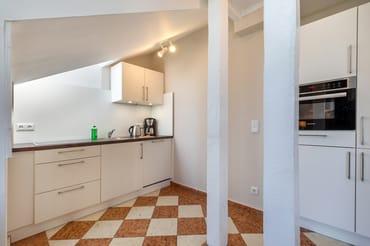 Die Küchenzeile im Wohnzimmer ist ausgestattet mit Geschirrspüler, Mikrowelle, Kühlschrank mit Eisfach, 4-Platten-Cerankochfeld etc.