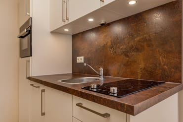 Die Küchenzeile mit Geschirrspüler und Mikrowelle.