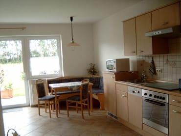 Essecke mit komplett ausgestatteter Küchenzeile (z.B. Backofen, Geschirrspüler, Mikrowelle, Kühlschrank mit Gefrierfach, Geschirr usw.) und Blick auf die Terrasse