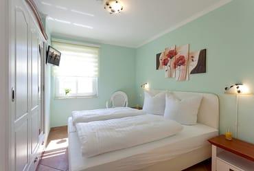 Das Schlafzimmer ist mit Doppelbett und Flat-TV ausgestattet.