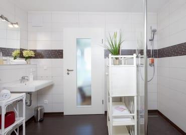 Das Bad en Suite, welches sowohl Zugang vom Schlafzimmer als auch vom Flur hat, spricht nicht nur wegen des großen ebenerdigen Duschbereiches an.
