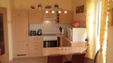 offene Küche mit Essplatz und Geschirrspüler, Toaster, Kaffeemaschine, Wasserkocher