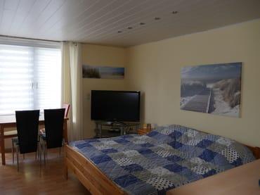 Wohnzimmer mit Doppelbett, Essplatz und großem LCD-TV