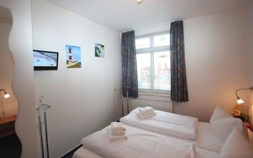 Das Schlafzimmer verfügt über ein Doppelbett, einen Kleiderschrank, ein Flachbildfernseher sowie Radiowecker.