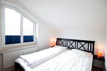 Das Schlafzimmer verfügt über ein Doppelbett, einen 3-türigen Kleiderschrank mit Spiegel.