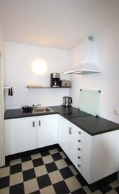 Die Küchenzeile verfügt über ein 2-Platten Ceranfeld, Kühlschrank mit Gefrierfach, Kaffeemaschine, Wasserkocher und Toaster.