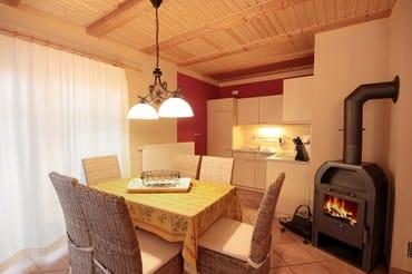 Wohnraum mit kompletter Küchenecke, seperatem Essplatz, Kamin und Zugang zur Terrasse