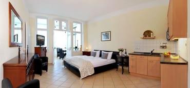 Der kombinierte Wohn- und Schlafbereich ist in warmen Farben gehalten.