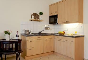 Die angrenzende Küchenzeile ist mit allem bestückt, was Sie für die Zubereitung Ihrer Lieblingsspeisen benötigen. Neben zwei Kochfeldern und einem Kühlschrank finden sich Geschirrspüler und Mikrowelle