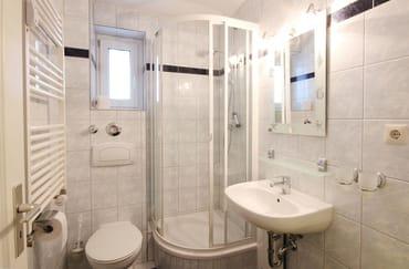 Das Badezimmer verfügt über Waschtisch, Dusche und WC.