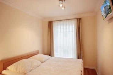 Das Hauptschlafzimmer beinhaltet ein großes Doppelbett sowie einen Flachbildfernseher.