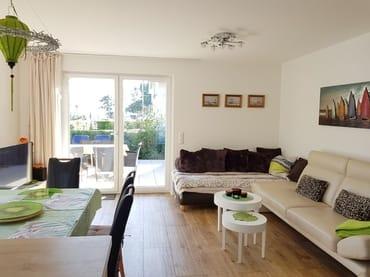 Ein breites, beiges Ledersofa in modernem Design sorgt für besten Sitzkomfort.