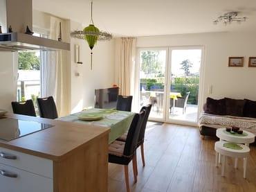 Heller Wohn- und Essbereich mit hochwertiger Küche. Die offene Küche ist komplett ausgestattet.
