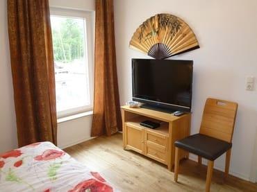 1. Schlafzimmer mit Massivholz-Doppelbett (Breite 1,60 m) und Fernseher.