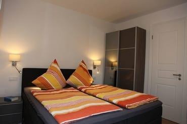 Hauptschlafzimmer mit Flachbildfernseher sowie Kleiderschrank und Kommode.