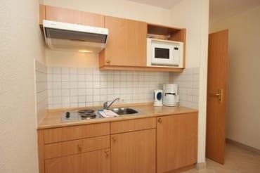 Die Küchenzeile ist komplett ausgestattet mit 2-Platten-Kochfeld, Mikrowelle, Kühlschrank mit Gefrierfach, Kaffeemaschine, Wasserkocher, Toaster, Mixer und Eierkocher.