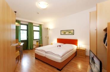 ... aber auch für reisefreudige Singles.   Der Wohnraum mit Flat TV ist in warmen Farben gehalten und mit einem hochwertigen Boxspringbett ausgestattet.