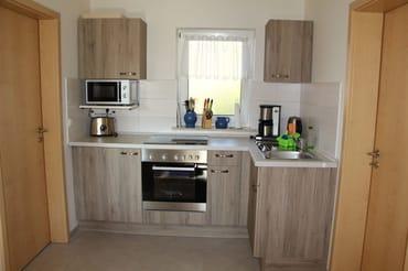 Küche mit Herd, Mikrowelle, Kaffeemaschine, Wasserkocher und Toaster