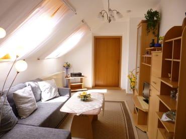 Wohnzimmer mit gemütlicher Couch, Flachbildfernseher und Radio
