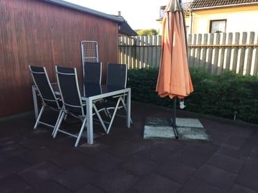 Grosse Terrasse mit Tisch und mobilen Sonnenschirm
