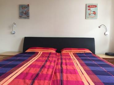 Schlafzimmer mit Doppelbett, Schreibtisch und TV.