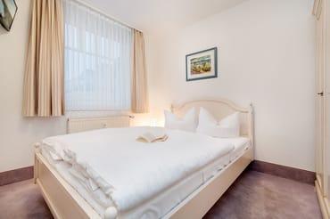 Im kleineren Schlafzimmer befindet sich ein Doppelbett (1,40m breit), ein Kleiderschrank und ein TV-Gerät.