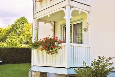 sonniger Balkon mit Sitzmöbeln und Sonnenschirm