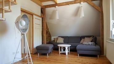 geräumiges Wohnzimmer mit bequemer Sitzecke und Treppe zur offenen Galerie im Spitzdach (Schlafplatz für 3. und 4. Person)