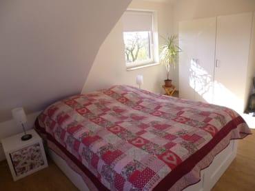 Schlafzimmer mit einem gemütlichem Doppelbett und Kleiderschrank