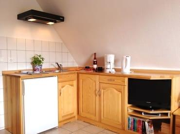 Küchenzeile (2-Plattenherd, Wasserkocher, Kaffeemaschine, Toaster) mit Entertainementbereich (Flachbild-TV, Bücherecke)