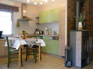 Offene Küche mit Esstisch und Kamin zum Wohnbereich gerichtet