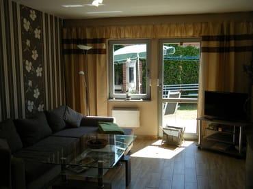 Wohnraum mit TV und Zugang zur Terrasse