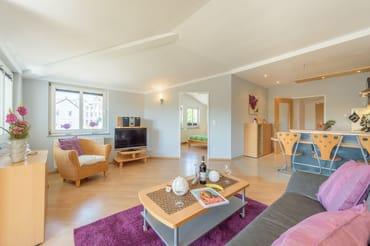 Der Wohnraum ist in modernen Farben gehalten, das gemütliche Sofa lädt zum Erholen und Entspannen ein.