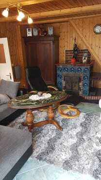 Hier schaut man von der Terasse aus in das gemütiche Wohnzimmer, mit dem rustikalen Kamin, der an kalten Tagen, selbst beheizt werden kann.