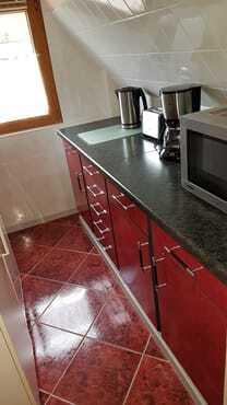Küchenzeile mit Microwelle, Kaffeemaschine, Toaster und Wasserkocher.