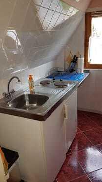 Kochmöglichkeit, mit Spühle, Kühlschrank und Arbeitfläche.